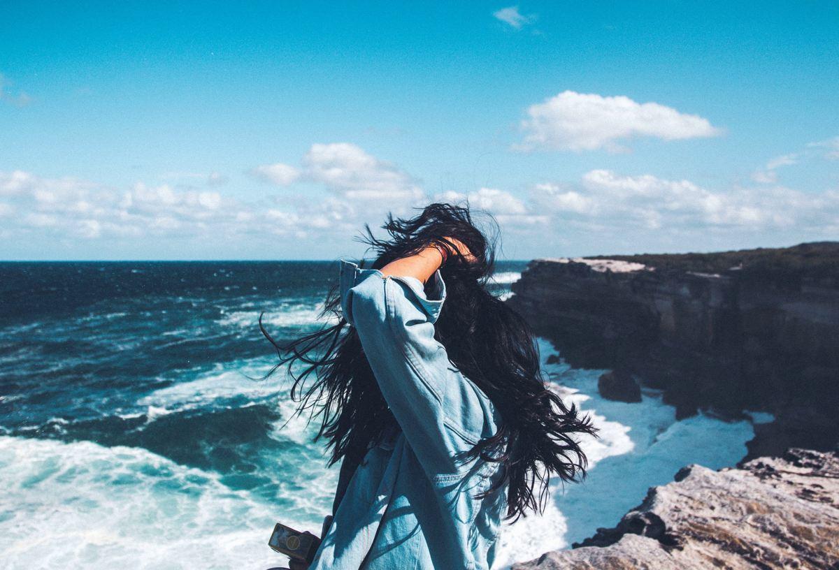 Junge Frau schaut von Klippe