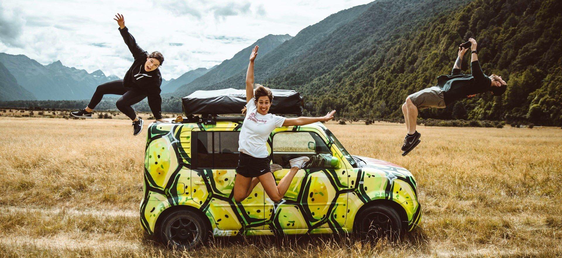 Gruppe von Work & Travellern posiert mit Auto