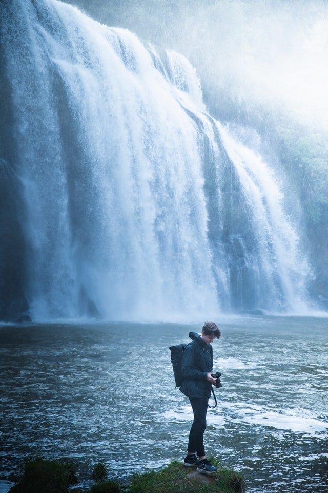Junger Mann vor Wasserfällen